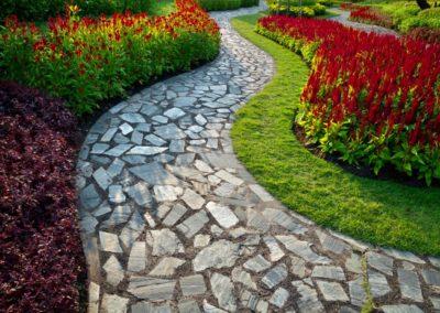 Allée composée de petites pierres avec parterres de fleurs de diverses couleurs