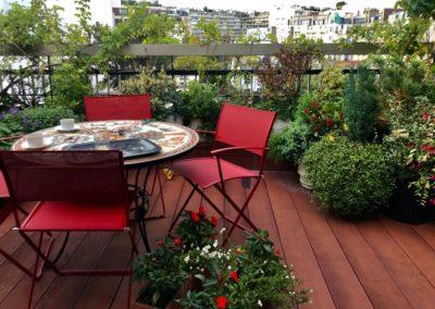 Table à manger entourée de végétaux sur toit terrasse