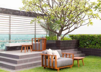 Aménagement d'un coin détente végétalisé avec fauteuils et petites tables en bois sur toiture d'immeuble