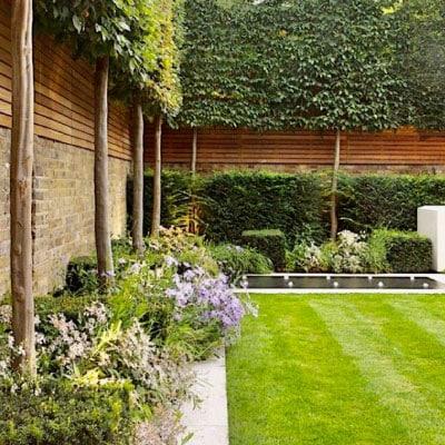 Aménagement d'un jardin cloisonné par mur brique et bois et composé d'arbres et de haies taillés