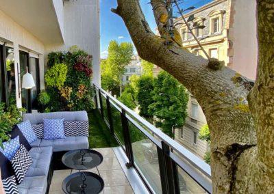 Création d'un balcon avec salon et vue sur mur végétal au fond