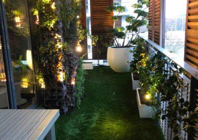 Balcon avec pelouse et végétaux sur les côtés et arbre type asiatique au fond
