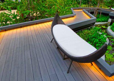 Allée en bois éclairages au sol avec banc posé sur le chemin verdoyant