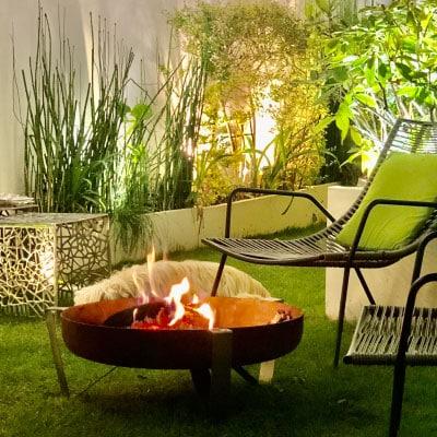 Brasero et chaises autour sur une terrasse pelouse éclairée