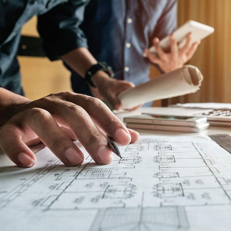 Hommes travaillant en bureau d'étude se penchant sur la conception de plans