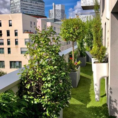 Balcon avec pelouse arbres et bac à fleurs fixés au mur vue sur immeuble