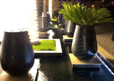 Décoration pots et plantes posés sur un plan d'eau éclairé vue de nuit