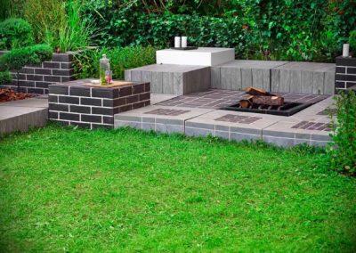 Jardin avec espace brasero et mobilier en brique et carrelage en pierre