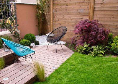 Jardin moderne avec terrrasse en bois et arbuste le long des palissades