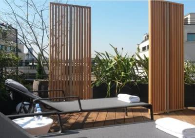Jardin terrasse d'un hotel de luxe avec chaises longues et palisade claustras bois