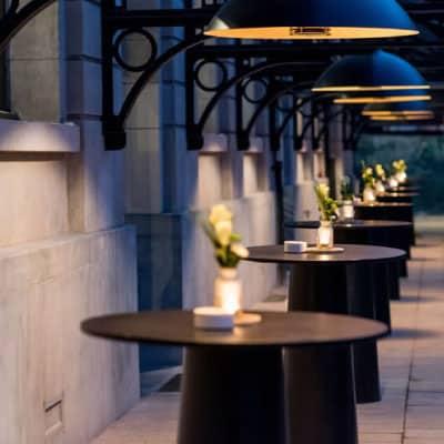 Mange-debouts en enfilade en extérieur éclairées par luminaires suspendus