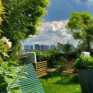 Terrasse avec pelouse mobilier et arbres vue sur immeuble