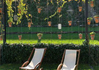 Pergola orignale composée de plantes et pots suspendus