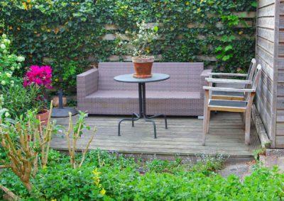 Coin terrasse en bois dans un renfoncement avec salon de jardin entouré de végétation