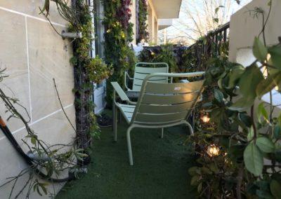 Création d'un balcon avec pelouse et végétaux vue dur 2 chaises basses