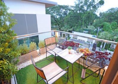 Réalisation d'un balcon carré et moderne avec table et chaise entouré de plantes