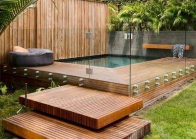 Terrasse bois dans le coin d'un jardin donnant sur une petite piscine