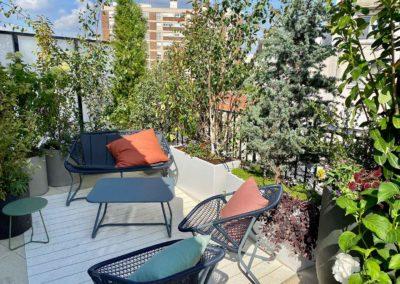 Salon extérieur sur le coin d'un balcon entouré d'arbustes