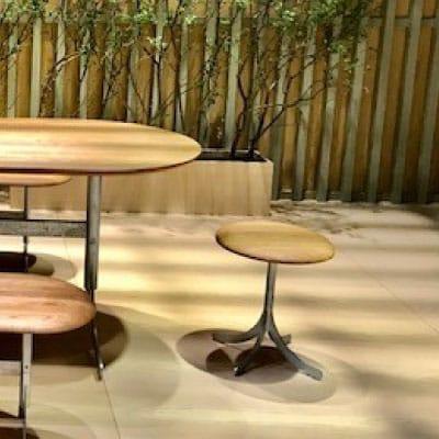 Tabouret assise en bois placé en bout de table sur une terrasse
