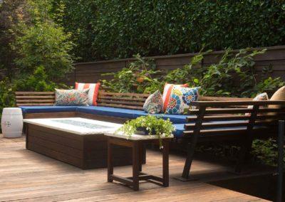 Terrasse en bois avec salon de jardin en bois entouré de végétation