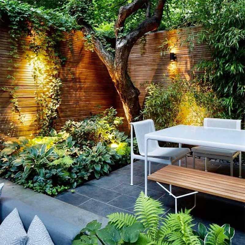Terrasse carrelage gris dans cour intérieur avec table et chaises végétatation tout autour