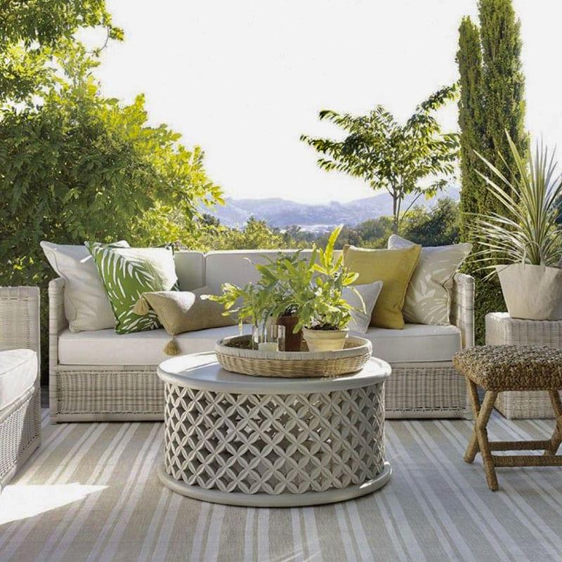 Terrasse avec salon extérieur table basse au centre entouré par végétation