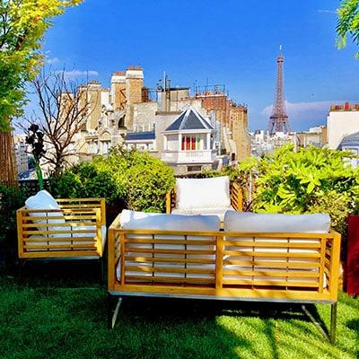 Toit terrasse pelouse au sol mobilier de jardin en bois vue sur tour Eiffel