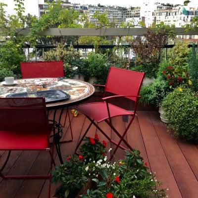 Transformation d'une terrasse sol en bois arbustes avec table et chaises rouge