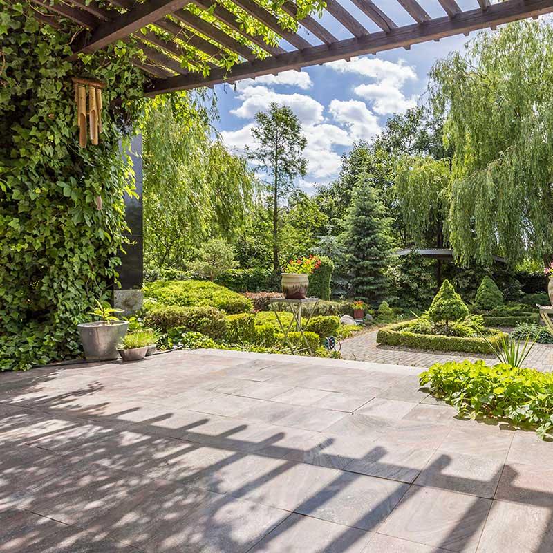 Végétalisation d'une terrasse pierre pergola en bois donnant sur une cour en pavés arbres et arbustes autour